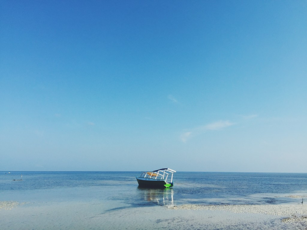 "Tiny boat ""castaway"" on the sunset side of Gili Air"